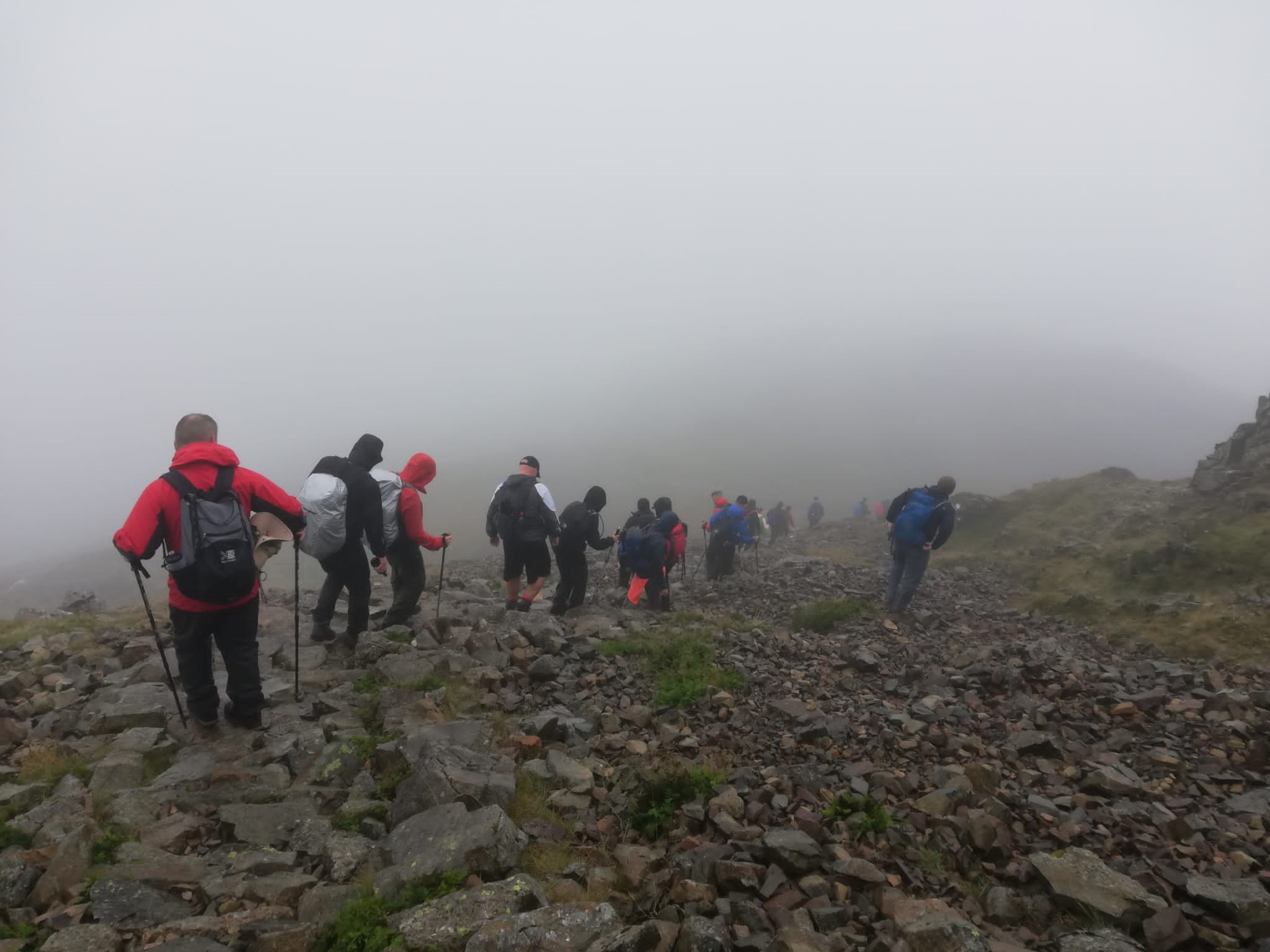Group of walkers, walking down a mountain in foggy conditions